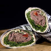 Slices of roast beef, roasted red pepper, arugula, spinach and garlic herb boursin cheese in a garlic herb wrap.