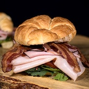 Smoked turkey breast, ham, bacon, tomato, mixed greens and dijonnaise on a buttery croissant.
