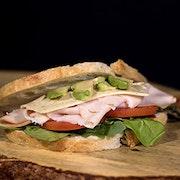 Smoked turkey breast, dill Havarti cheese, avocado, tomato and mixed greens on artisan sourdough bread.