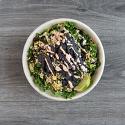 not your average tex-mex bowl kale, brown rice, black beans, roasted corn, red onion, avocado, feta cheese, tortilla chips, lime wedge, cilantro lime dressing, honey sriracha drizzle  ADD ROASTED CHICKEN THIGHS OR BBQ TOFU
